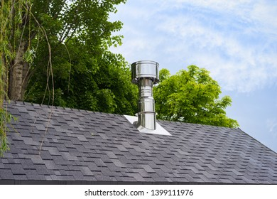 Close up view on bitumen asphalt roofing shingles and stainless steel chimney pipe.