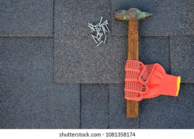 Close up view on bitumen shingles on a roof  with hammer,nails and stationery knife background.