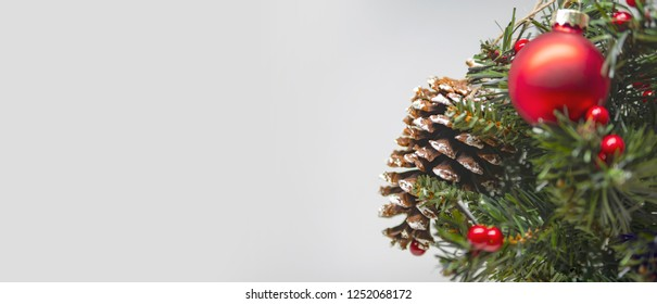 Close up view on Christmas tree decorated with red bauble and a cone, space for text