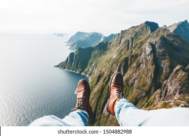 Close Up view on feet wearing hiking boots. Man tourist sitting on the edge cliff mountains above sea