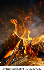 Close up view on a fire above burning woods in a firepit