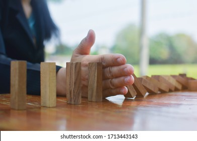 Close up view on hand of business woman stopping falling blocks on table for concept about taking responsibility.