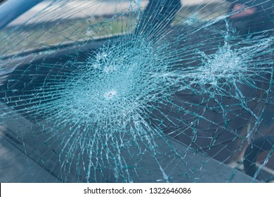 Close up view on a heavily shattered windshield of a car