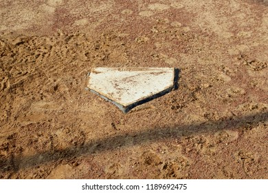 A close view on the home plate area on the baseball dirt infield on a a sunny day.