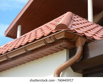 Close up view on House Metal Roof Problem Areas for Rain Gutter Waterproofing Outdoor. Home Guttering, Gutters, Plastic Guttering System, Guttering & Drainage Pipe Exterior. Roofing repair.