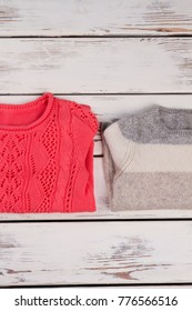 Close view on knitted sweaters. Woolen and cotton, stylish warm clothes. Handmade, knitting concept.