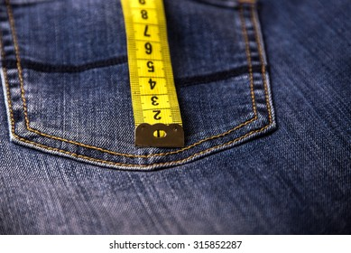 Close view on measure tape on a back pocket of blue denim. Background and texture.