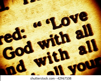 Close up view on a part biblical commandment of unconditional love to God and the neigbour. Focusing on the words: Love - God with all. Bible -Gospel of Luke ch. 10, v. 27. (Bible in Macro series)