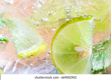 Close up view on piece of lemon lime in lemonade or gin tonic with side view, copy space. Summer beverage wallpaper or background. Macro concept of lemon gin tonic to present surface or texture.