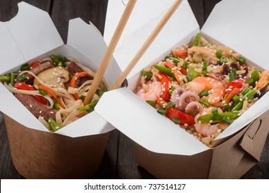 Close view on rice and Udon noodles in open takeaway boxes and chopsticks. Nutritious mix of chicken meat, vegetables and seafood.