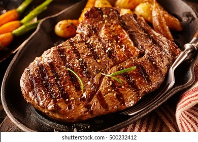Close up view on serving of marinated grilled rib eye steak with potatoes in cast iron plate and fork