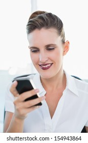 Close up view on smiling businesswoman using smartphone in bright office