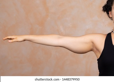 A close up view on the stretched out arm of a Caucasian lady. Saggy muscle and fat is seen in the upper arm area. Commonly called bingo wings and corrected with plastic surgery.