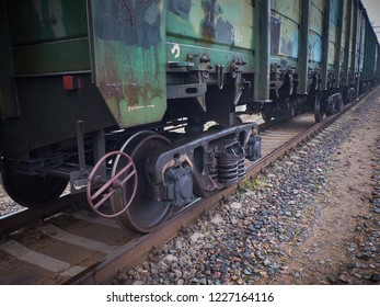 Close up view on used rusted railway freight car bogie with wheel sets with axleboxes, coil springs. Freight train on the railway tracks with concrete sleepers