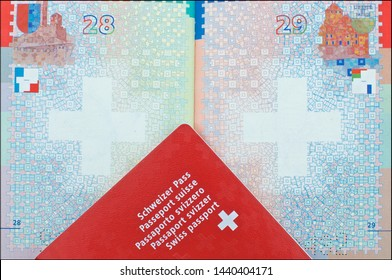 Close up view of one Swiss passport laid over another open passport in the background