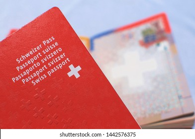 Close up view of one Swiss passport with a blurred open swiss passport on the background