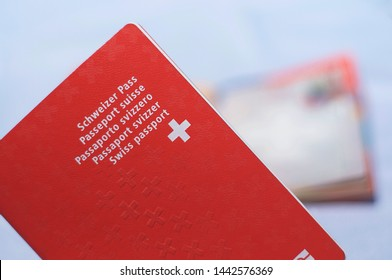 Close up view of one Swiss passports with a blurred open swiss passport on the background