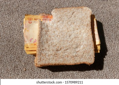 A close up view of one and two hundred rand notes in between a brown bread snadwich that has a bite taken out the top corner