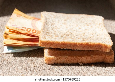 A close up view of one and two hundred rand notes in between a brown bread snadwich