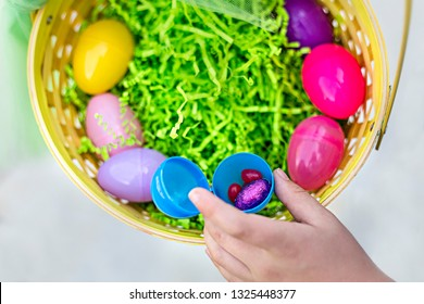 Close up view of an open plastic egg with Easter candy in it. A hand is pulling out candy out of the Easter basket with other eggs and paper grass in it