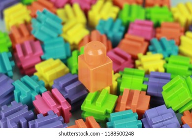 Close up view of orange toy block with background of colorful children building blocks.