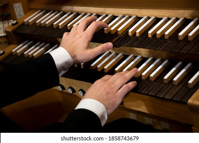 Close up view of a organist hands playing a pipe organ - Shutterstock ID 1858743679