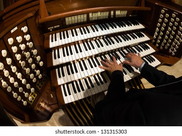 Close up view of a organist playing a pipe organ.