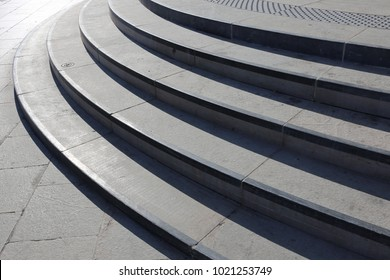 Close up view of outdoors stone staircase. Long grey curved steps lighted by the sun. Elegant architectural design. Pattern with curved lines and shadows.Abstract urban picture taken a sunny day.