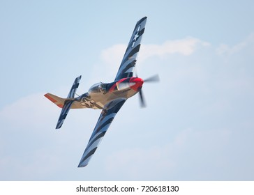 Close view of P-51D Mustang (WWII American fighter plane) in a turn, against the cloudy sky and in beautiful light