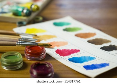 Close up view of paints in tubes, paint jars with brushes and color palette on wooden table