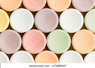 Close up view of pale multicolored circular vitamins or tablets sitting on top of wooden table surface