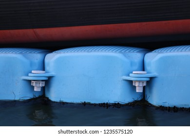 Close up view of part of a black and red boat with clear blue floaters. Abstract maritime image with colored lines of a ship in a marina. Colorful shapes on the water.