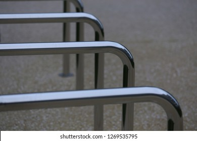 Close up view of pattern of curved inox tubes used to place bikes in a french city. Abstract urban image with curving lines. Metallic lighted objects with vertical and horizontal shapes.