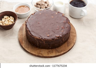 Close up view of Peanut Butter Chocolate Caramel Cheesecake Pie and cup of coffee on dining table with linen tablecloth. A Sweet Coffee Break concept