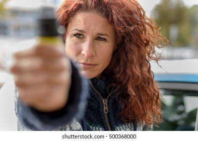 Close up view of pepper spray in hand of serious adult woman in curly red hair standing outside near automobile door