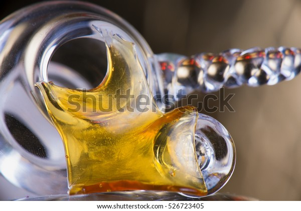 Close up view of a piece of cannabis oil concentrate aka shatter with glass rig bowl and nail