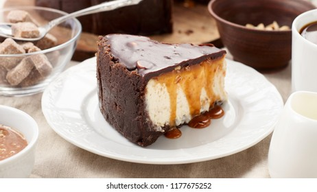 Close up view of a piece of Peanut Butter Chocolate Caramel Cheesecake Pie and cup of coffee on dining table with linen tablecloth. A Sweet Coffee Break concept