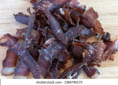A close up view of a pile of south african biltong on a wood cutting board