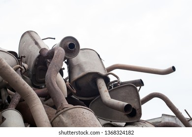 Close view pile of used mufflers at car workshop. Old car mufflers Isolated on a white background. Lot of exhaust pipes stacked in absolutely no order