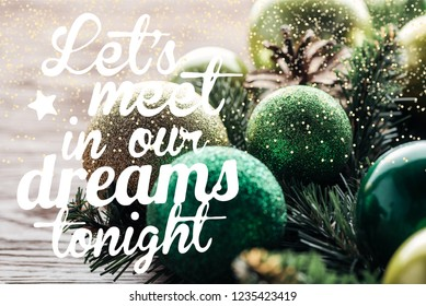 """close up view of pine tree wreath with green christmas balls on wooden background with """"lets meet in our dreams tonight"""" inspiration"""