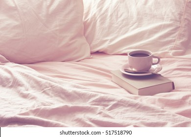 Close up view of pink, cotton open bed space. Coffee cup and saucer rest on vintage book. Space for copy.