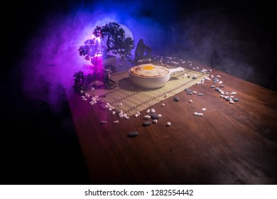Close up view of plate with japanese food inside. Japan traditional food on wooden table with decoration of bonsai tree and moon on toned foggy background.