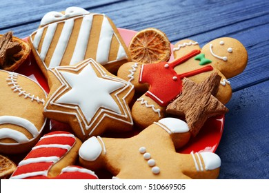 Close up view of plate with tasty Christmas cookies on wooden table