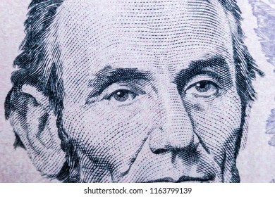 Close up view Portrait of Abraham Lincoln on the one five dollar bill. Background of the money. 5 dollar bill with Abraham Lincoln eyes macro shot. Money background. Face portrait