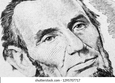 Close up view Portrait of Abraham Lincoln on the one five dollar bill. Background of the money. 5 dollar bill with Abraham Lincoln eyes macro shot. Money background. Face portrait. Black and white
