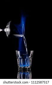 close up view of pouring burning sambuca alcohol drink into glass process on black background