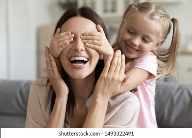 Close up view preschool daughter closes her mother eyes with hands play together have fun spend funny leisure at home, loving kid girl prepare surprise for beautiful mom showing care and love concept