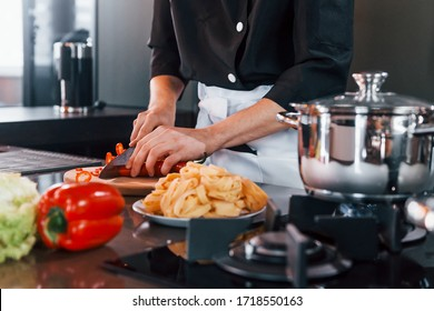 Close up view of professional young chef cook in uniform that working on the kitchen.