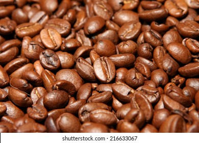 Close view of randomly stacked coffee beans fills the frame. Roasted beans in shades of brown color forming a plane. Visible details, indoor lighting.