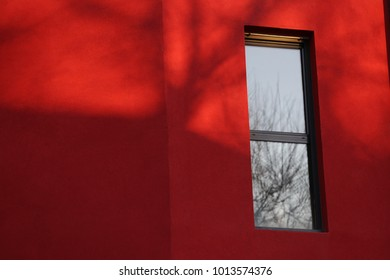 Close up view of a rectangular vertical window in a red wall. Isolated element on a painted surface. Detail of a colorful facade building and one window. Abstract urban picture. Minimalist figure.